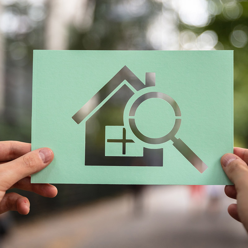 Person holding a cutout of a house and magnifying glass on green paper